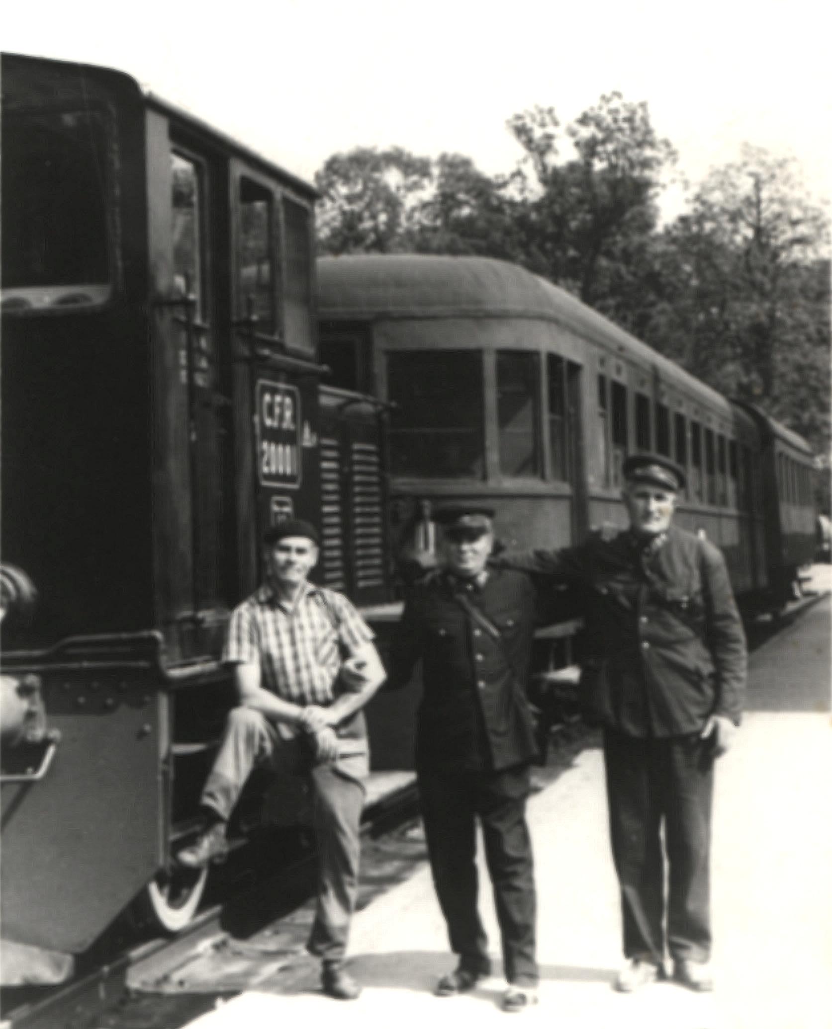"""Juli 1973. Die """"Kleine Bahn"""" mit der Diesellok 20.001 am Bahnhof im Kurpark. Im Bild die Schaffner Aurel Boncea (rechts), Aurel Negrea (Mitte) und Lokführer Ulmeanu (links)."""