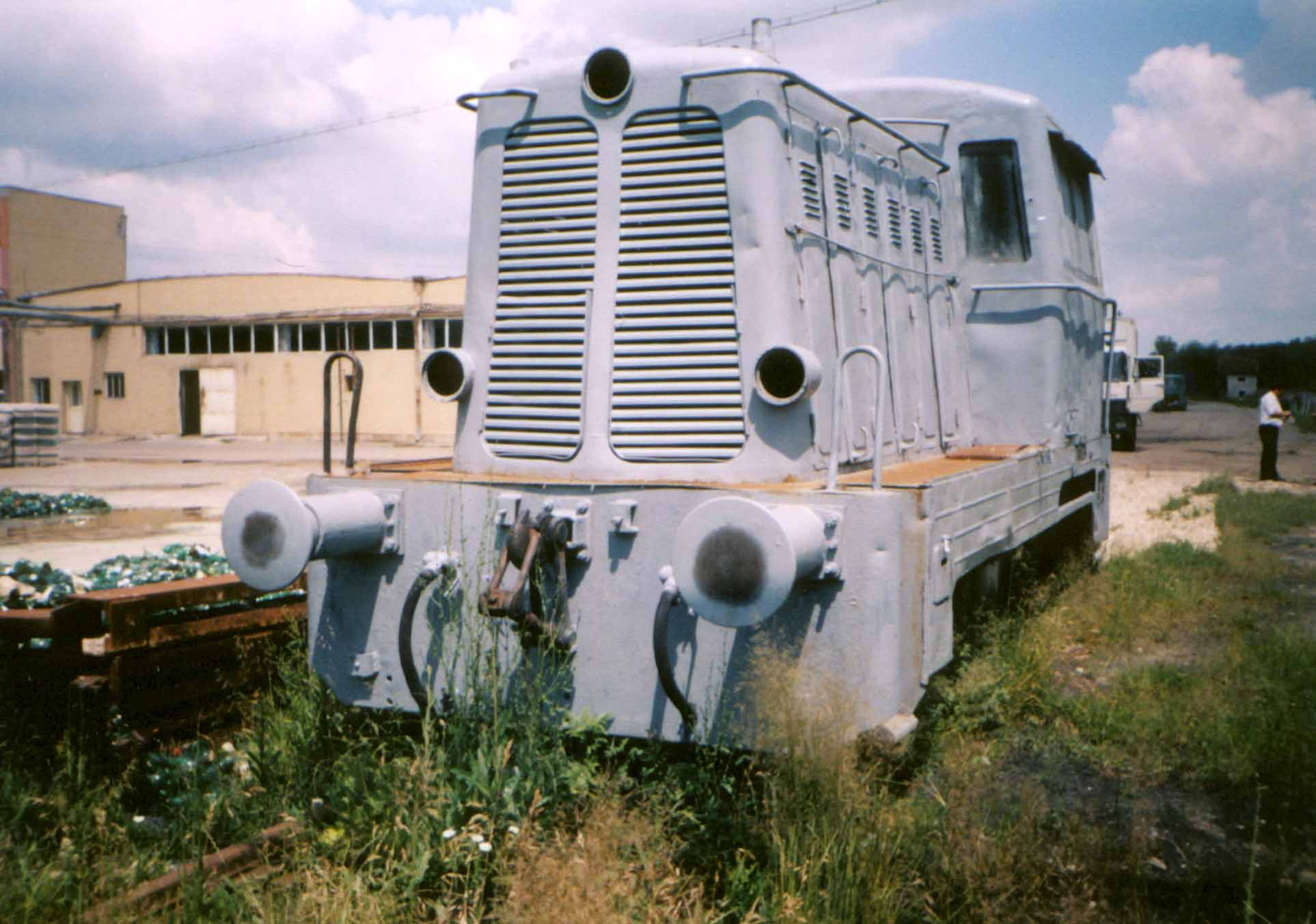 """Die Tatra-Lok in der neuen """"Apemin"""". Die Strecke im Hintergrund ist überasphaltiert und wird als Zufahrt für LKW' s benutzt, da auf einen Bahnbetrieb verzichtet wurde."""